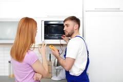 Dona de casa e reparador perto do forno micro-ondas fotos de stock
