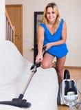 Dona de casa em hoovering ocasional em casa Foto de Stock