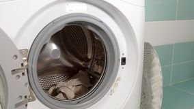A dona de casa enche a máquina de lavar da cesta de lavanderia e os fechamentos fazem à máquina a porta video estoque