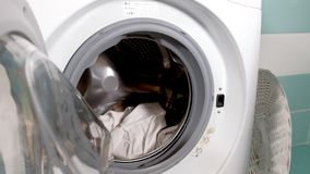 A dona de casa enche a máquina de lavar da cesta de lavanderia e os fechamentos fazem à máquina a porta filme