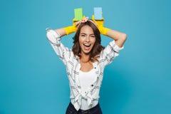 Dona de casa engraçada feliz 20s em luvas de borracha amarelas para o prot das mãos fotografia de stock