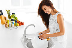A dona de casa está fazendo a lavagem da louça Vegetais no fundo imagens de stock