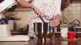 A dona de casa está misturando ingredientes em uma bacia grande do metal na cozinha vídeos de arquivo