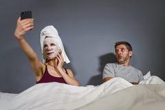 Dona de casa excêntrica com máscara facial e a toalha da composição que tomam o selfie na cama e marido com expressão desesperada fotografia de stock