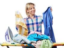 Dona de casa feliz bonita da mulher que guarda a lavanderia para passar Fotografia de Stock