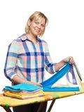 Dona de casa feliz bonita da mulher que guarda a lavanderia para passar Fotos de Stock
