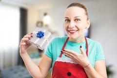 Dona de casa feliz e surpreendida que guarda um presente ou um presente fotos de stock