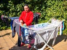 a dona de casa feliz que mantém a roupa molhada apenas removida da máquina de lavar na linha de lavagem pôs sobre o terraço de um fotos de stock