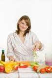 A dona de casa joga o aipo desbastado em uma bacia de salada Fotos de Stock Royalty Free