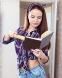 A dona de casa lê o livro de receitas imagens de stock