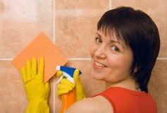 A dona de casa limpa uma telha Foto de Stock