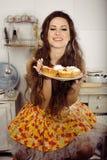 Dona de casa louca em comer de sorriso da cozinha Fotografia de Stock Royalty Free