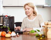 Dona de casa madura de sorriso com o caderno na cozinha Fotos de Stock Royalty Free