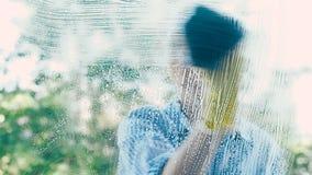 A dona de casa na camisa limpa o vidro de janela com o pano molhado azul vídeos de arquivo