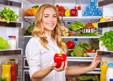 A dona de casa na cozinha toma a pimenta vermelha do refrigerador Imagem de Stock Royalty Free