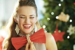 Dona de casa na moda de sorriso que guarda o guardanapo de jantar vermelho como o laço fotografia de stock