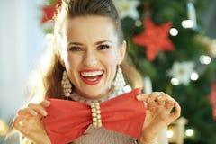 Dona de casa na moda de sorriso que guarda o guardanapo de jantar vermelho como o laço fotos de stock royalty free