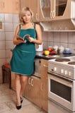 A dona de casa no avental verde na cozinha fotos de stock