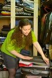 A dona de casa no wardrobe embala uma mala de viagem Imagem de Stock Royalty Free