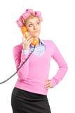Dona de casa nova bonita com rolos do cabelo que fala em um telefone imagens de stock