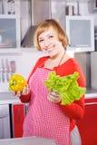 Dona de casa nova bonita na cozinha vermelha Imagens de Stock