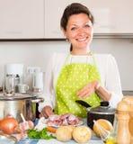 A dona de casa nova cozinha a carne com arroz Foto de Stock Royalty Free