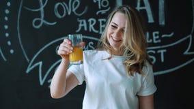 Dona de casa nova da mulher na cozinha em casa para beber o suco de laranja caseiro fresco Esprema o suco da laranja video estoque