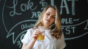 Dona de casa nova da mulher na cozinha em casa para beber o suco de laranja caseiro fresco Esprema o suco da laranja vídeos de arquivo