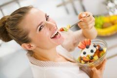 Dona de casa nova feliz que come a salada de frutos Fotografia de Stock Royalty Free