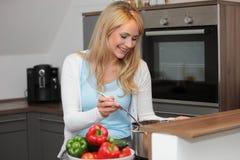 Dona de casa nova feliz que cozinha o jantar fotos de stock royalty free