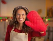 Dona de casa nova feliz que mostra a luva vermelha da cozinha Imagem de Stock