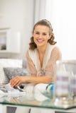Dona de casa nova feliz que senta-se na sala de visitas imagens de stock royalty free