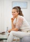 Dona de casa nova que senta-se na sala de visitas imagem de stock