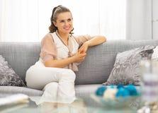 Dona de casa nova que senta-se na sala de visitas fotografia de stock