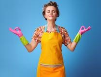 Dona de casa nova relaxado no avental amarelo na ioga fazendo azul imagens de stock