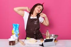A dona de casa ou o padeiro feliz que esticam as mãos após o dia cansado na cozinha, terminam amassar a massa com expressão facia foto de stock royalty free