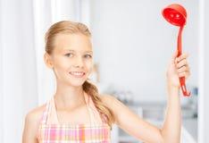 Dona de casa pequena com a concha vermelha na cozinha Fotos de Stock