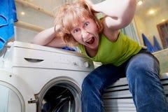 A dona de casa perto da m?quina de lavar na sala do banho e e na ela ? muito cansado do lavagem imagem de stock