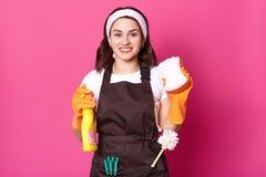 Dona de casa positiva, bonito alegre que guarda a toalha de rosto e o detergente em ambas as mãos, tendo a escova do toalete e os fotografia de stock royalty free