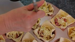 A dona de casa prepara o queijo da salsicha coze, lubrifica a massa com os ovos fecha-se acima filme