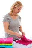 Dona de casa que dobra toalhas coloridas Fotos de Stock Royalty Free