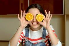 Dona de casa que guarda fatias alaranjadas na frente de seus olhos e sorrisos Fotos de Stock Royalty Free
