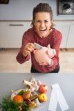 Dona de casa que põe o dinheiro no mealheiro Fotos de Stock