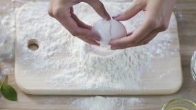 Dona de casa que quebra o ovo na farinha na placa da cozinha, fazendo a massa pela receita da torta filme