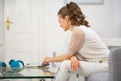 Dona de casa que senta-se na sala e que lê o compartimento imagens de stock royalty free