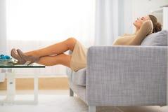 Dona de casa relaxado que coloca no divã na sala de visitas imagens de stock