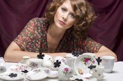 Dona de casa Tired Uma mulher bonita que senta-se em uma tabela com lotes do serviço de café dos pires dos copos Fotografia de Stock Royalty Free