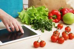 A dona de casa usa um tablet pc na cozinha imagens de stock royalty free