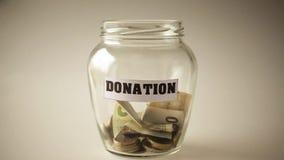 Donación, ahorros del dinero en un tarro metrajes
