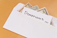 Donaciones del efectivo en sobre fotos de archivo